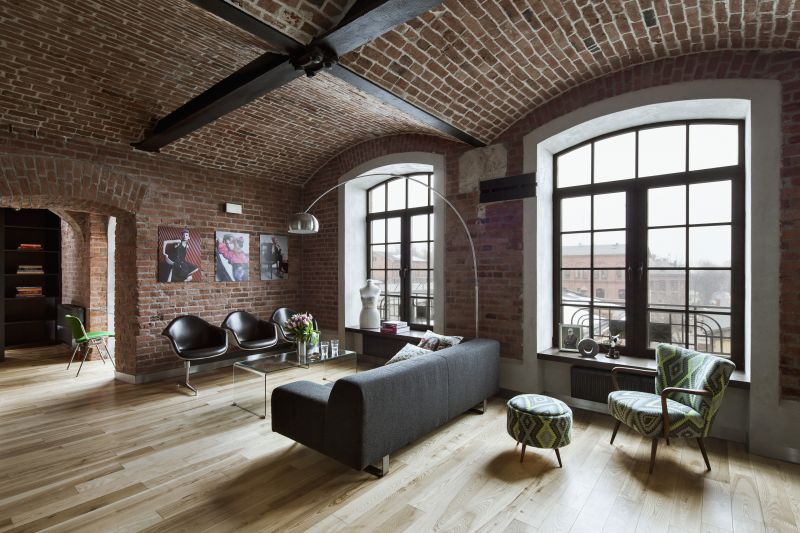 Open-plan interior with armchair, footstool & lounge area with arc lamp in industrial ambiance